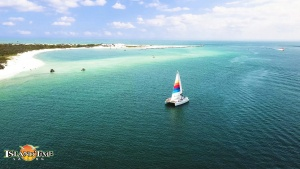 image of an island time sailing boat out on the water