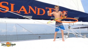 image of a boy playing with two hullu hoops during a trip on an Island Time Sailing ship