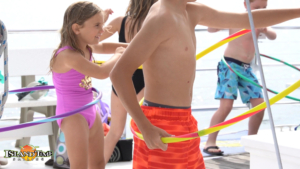 kids playing with hullu hoops on an island time sailing boat