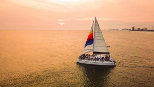 image of a boat sailing out on the water during a sunset cruise