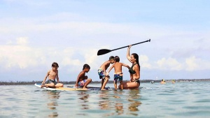 image of a family out on the water floating on a surfboard