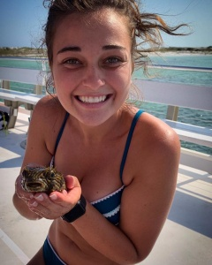 image of a woman holding an animal found during a snorkeling trip hosted by Island Time Sailing