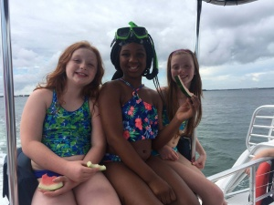image of three kids on a boat eating watermelon during an Island Time Sailing cruise