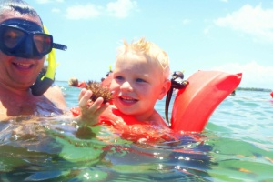 image of a child and their parent holding a sea urchin found during a snorkeling trip